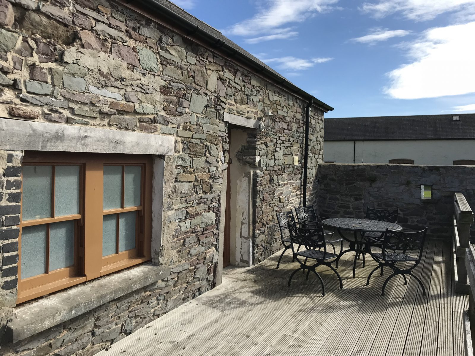 Terrace seating outside cottage at The Corran Resort